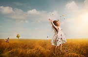 A little girl in in a field of butterflies raising her hands to the sky.