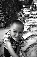 Portrait of a kid looking at the camera and smiling. Ping'an area, Guangxi, China, Asia