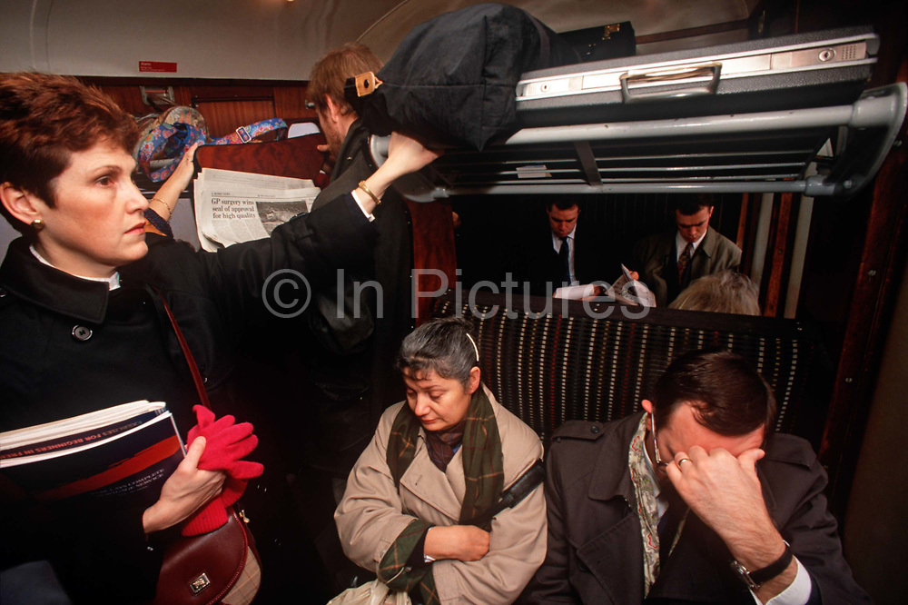 1990s passengers sit and stand in an overcrowded train carriage in the City of London aka The Square Mile, the capitals financial centre, on 18th February 1992, in London, England.