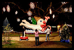 Dec 30th, 2005. New Orleans, Louisiana. Celebration in the Oaks at City Park. As New Orleans returns to a small sense of normalcy, people came out to see the lights and to enjoy the rides and amusements in City Park. Locals stop to photograph Mr Bingle, a New Orleans cult figure attached to a Cajun Christmas..