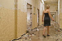 Blonde woman in dress walking down hall of abandoned building