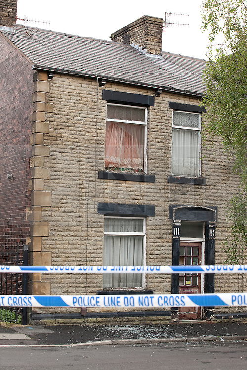 © Licensed to London News Pictures. 27/06/2012. Oldham , UK . A large explosion , believed to be caused by gas , has brought down at least one house in an Oldham terrace. A house with a smashed first floor window and glass in the street below . Photo credit : Joel Goodman/LNP