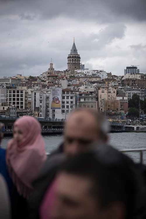 The Galata Tower, an Istanbul landmark built by the Genoese in 1348, rises in the distance as passengers disembark a ferry on the Bosphorus Strait.