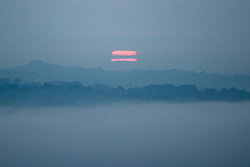 © Licensed to London News Pictures. 13/09/2016. Ilkley UK. The sun breaks through the low lying fog this morning over the town of Ilkey on what is predicted to be the hottest day in September. Photo credit: Andrew McCaren/LNP