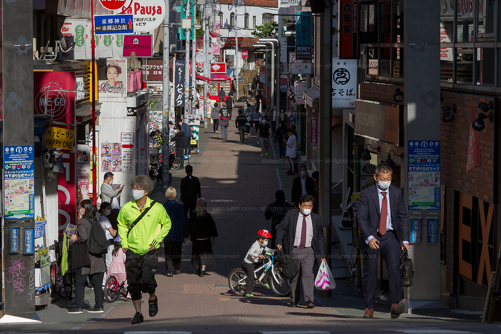 People wearing surgical masks in a  much quieter than usual Takashita Dori in Harajuku, Tokyo, Japan. Thursday May 7th 2020. he month-long state of emergency declared by the Japanese government in response to the COVID-19 pandemic was due to end on May 7th but was extended to May 31st despite Japan appearing to have avoided the high infection and mortality rates of some countries. Areas like Shibuya have many businesses shuttered and closed and the streets are a lot quieter than usual.