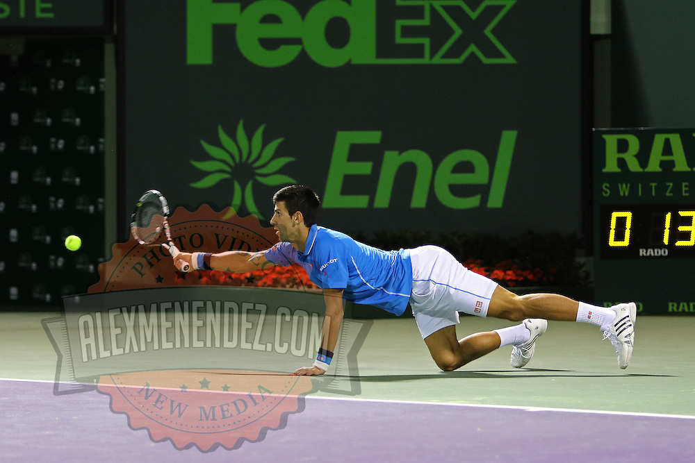 Novak Djokovic, of Serbia dives in an attempt to return a shot from Martin Klizan, of Slovakia, during their match at the Miami Open tennis tournament on Saturday, March 28, 2015 in Key Biscayne, Florida. Djokovic defeated Klizan 6-0, 5-7, 6-1. (AP Photo/Alex Menendez)