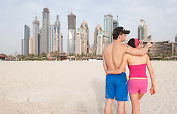 Young couple on beach at Jumeirah Beach resort district with high rise buildings to rear in Dubai, United Arab Emirates,UAE