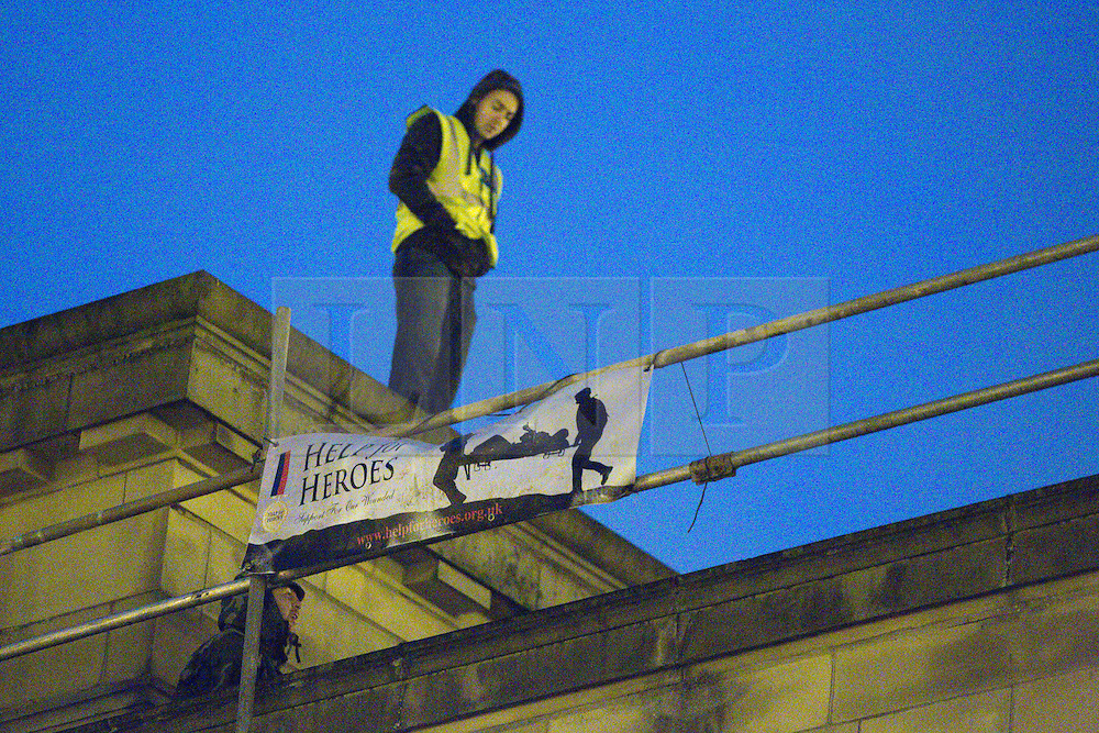 "© licensed to London News Pictures. Bury, UK  03/03/2012. Following a National Front demonstration in nearby Heywood, groups known as the ""North West Infidels"" and the ""Combined Ex Forces"", splinters of the EDL and other far-right organisations, are staging a rooftop protest on Bury Town Hall. Police said the group had climbed up scaffolding at the side of the Town Hall to gain roof access. They have affixed banners stating ""Hang paedo scum"" along with nationalist slogans. Photo credit should read Joel Goodman/LNP"