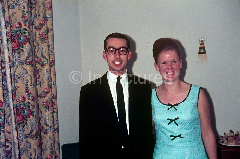 Young European couple at their engagement party in Blantyre, Malawi in the mid-1960s.  Standing together against a plain wall in a small house or bungalow, they look happy with the prospect of married life - both smiling broadly next to a patterned curtains (drapes).