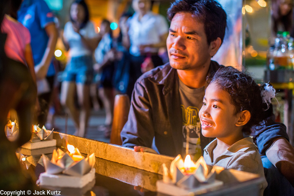 28 NOVEMBER 2012 - BANGKOK, THAILAND: A man and his daughter watch their krathong float in a small pool at Wat Yannawa in Bangkok. Loy Krathong takes place on the evening of the full moon of the 12th month in the traditional Thai lunar calendar. In the western calendar this usually falls in November. Loy means 'to float', while krathong refers to the usually lotus-shaped container which floats on the water. Traditional krathongs are made of the layers of the trunk of a banana tree or a spider lily plant. Now, many people use krathongs of baked bread which disintegrate in the water and feed the fish. A krathong is decorated with elaborately folded banana leaves, incense sticks, and a candle. A small coin is sometimes included as an offering to the river spirits. On the night of the full moon, Thais launch their krathong on a river, canal or a pond, making a wish as they do so.    PHOTO BY JACK KURTZ