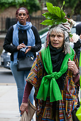 London, UK. 14th June, 2018. A woman dressed in Grenfell green arrives for the Grenfell Memorial Service at St Helen's Church.