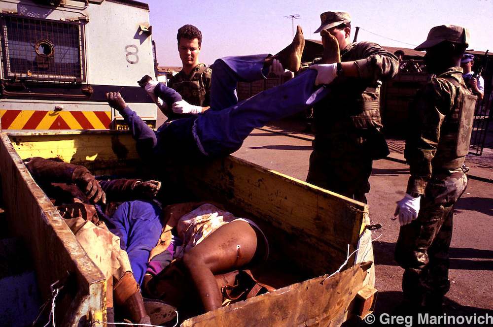 960403JS01:SAFRICA:UNREST:TOWNSHIPS:JUL93 - Police officers load corpses into an open back trailer after a night's violence  between ANC and IFP supporters in Tokoza township.  Death toll was up to 60 that week-end in the township.(Photo by Joao Silva/PictureNET)sun grim mass murder