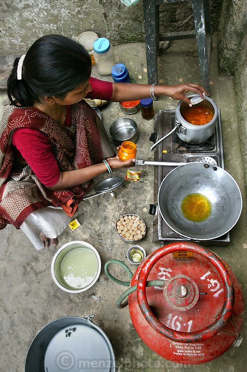 Rickshaw driver Munna Kailash's wife Meera adds turmeric to dal that she cooked in a pressure cooker as she prepares lunch for her husband in their courtyard in Varanas, India.  (From the book What I Eat: Around the World in 80 Diets.) MODEL RELEASED.