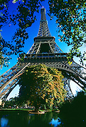 Eiffel Tower and park with blue sky and pond.