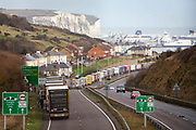 Lorries line up on the M20 motorway to use the BREXIT Dover Tap contraflow system into the Eastern Dock of the Port of Dover where the cross channel port is situated with ferries departing here to go to Calais in France on the 18th December 2020, Dover, Kent, United Kingdom. Dover is the nearest port to France with just 34 kilometres 21 miles between them. It is one of the busiest ports in the world. As well as freight container ships it is also the main port for P&O and DFDS Seaways ferries.