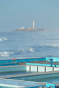 High angle view of man fishing on lido with rough sea and lighthouse in background, Casablanca, Morocco