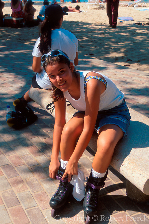 PUERTO RICO, SAN JUAN World Heritage Site Condado Lagoon Beach, teenager tying laces on her roller-blades