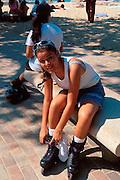 PUERTO RICO, SAN JUAN World Heritage Site Condado Lagoon Beach, teenager tying laces on her roller-blades