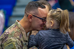 A Soldier with 1st Battalion, 32nd Infantry Regiment, 1st Brigade Combat Team, 10th Mountain Division (LI) greets his daughter after a welcome home ceremony held in 1-32IN's honor after redeploying from Djibouti at Magrath Sports Complex, Fort Drum, N.Y., Oct. 2, 2018. (U.S. Army photo by SSG James Avery, 1BCT10MTN Public Affairs)