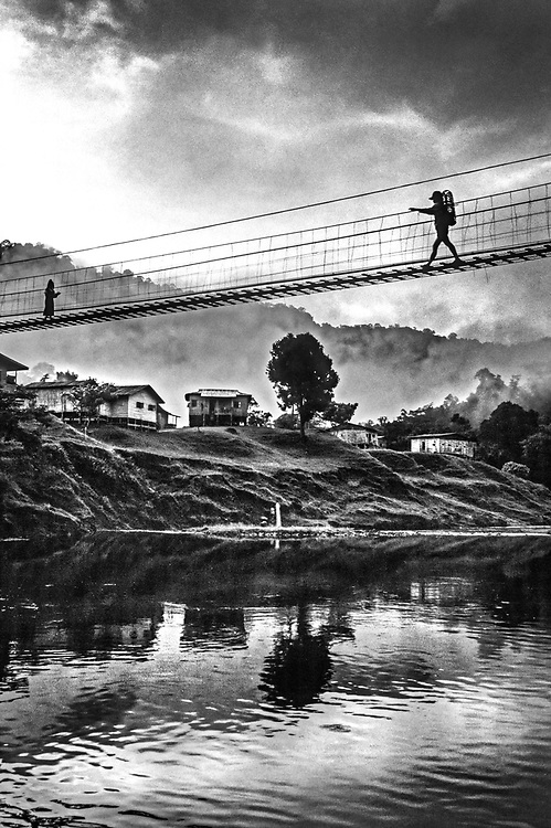 Two people crossing a typical Malaysian wooden rope bridge, Malaysia, Sabah, Borneo 1992
