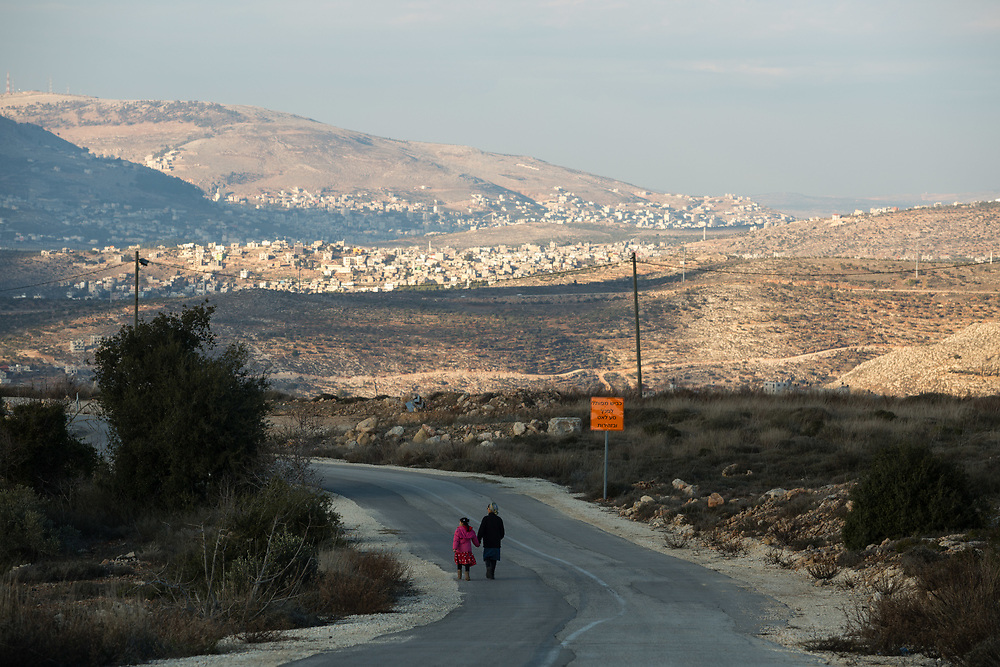 A Jewish mother and her daughter walk down a road with a view of Palestinian villages in the background, at the West Bank Jewish settlement of Eli, located south of the Palestinian West Bank town of Nablus, on January 1, 2017.