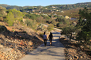 Two women walking village of Lliber, Marina Alta, Alicante province, Spain