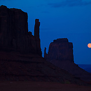 Full moon rising over the mittens in Monument Valley, Utah.