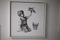 Banksy artwork at Southampton General Hospital in a foyer near the emergency department. It shows a young boy kneeling by a wastepaper basket  photo by Michael Palmer