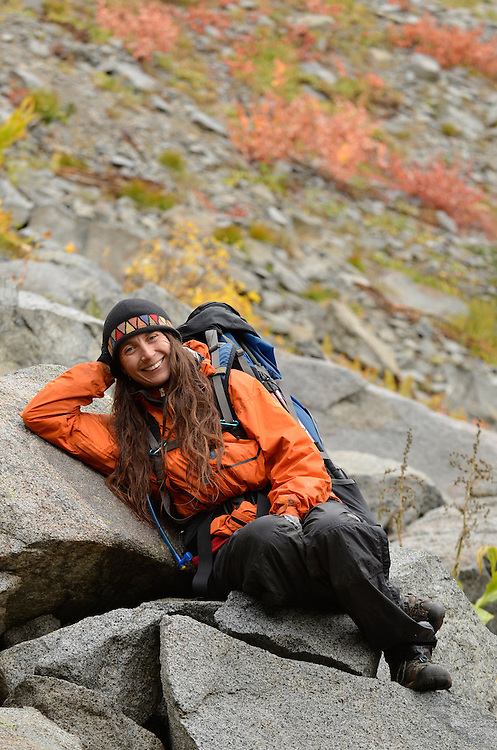 Woman resting on boulders on a backpack trip in Oregon's Wallowa Mountains.