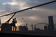 A photographer with a tripod prepares to photograph the sunset over the Yokohama skyline from Osanbashi Pier in Yokohama, Kanagawa, Japan. Saturday October 23rd 2010