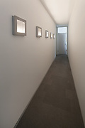 Interior of a modern house, long corridor with paintings lit
