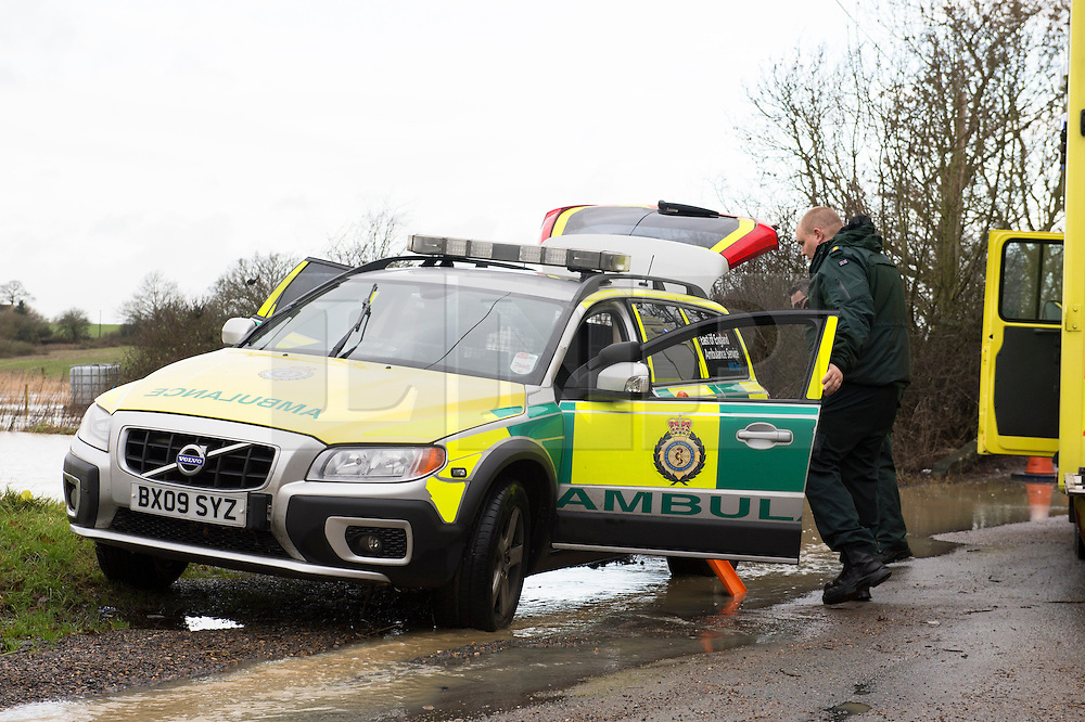 © Licensed to London News Pictures. 24/12/2013. Billericay, UK. UK Weather. After a night of torrential rain and wind many roads became flooded across the south of England. In Billericay, an East of England Ambulance Service Volvo paramedic vehicle became a victim of the water. It became stuck in the flood water and was pulled clear by another vehicle. Other units attended to tranfer the emergency equipment out of the vehicle.  Photo credit : Simon Ford/LNP/LNP