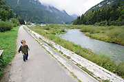 A young toddler walking along a stream. Photographed in Italy, Dolomites Mountains