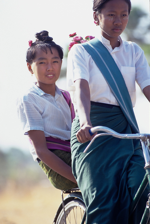 Young female students in uniform on bicycle, Magwe Division, Central Myanmar,