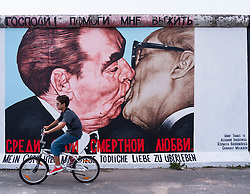 Boy cycles past mural of Brezhnev kissing Honecker at East Side Gallery at former Berlin Wall in Friedrichshain/Kreuzberg in Berlin Germany