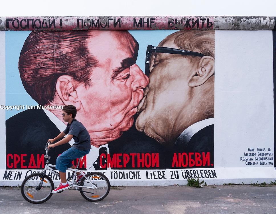 Boy cycles past mural of Brezhnev kissing Honecker at East Side Gallery at former Berlin Wall in Friedrichshain/Kreuzberg in Berlin Germany