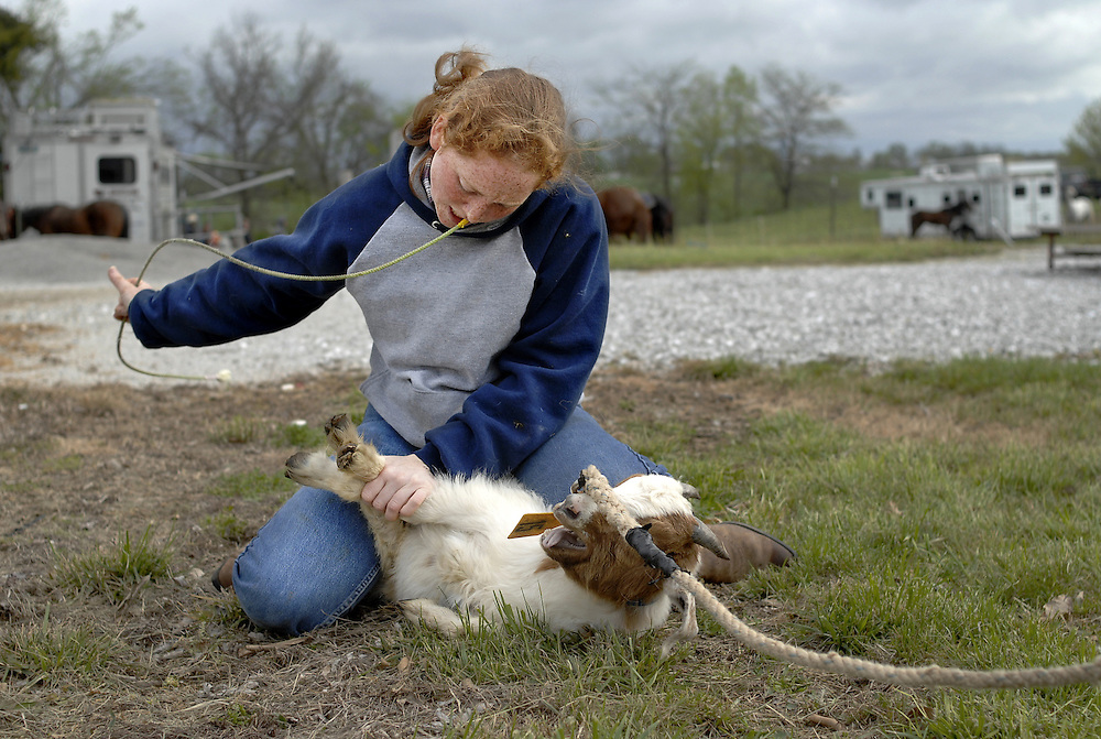 """Casey Chasteen, 18, is a two-time Missouri state champion in goat tying. The Rock Bridge High School senior is up early on a Saturday. Most of her classmates are probably sleeping in, especially on this cold, windy spring morning, but for Casey every weekend is another rodeo.<br /> <br /> Her smile is bright under a small straw hat. Her red hair bobs in the wind. She has big responsibilities. As state champion, Casey is the event director for goat tying. She makes sure the animals have been properly vetted, tied three times and organized by size.<br /> <br /> As part of this process, participants each take a turn tying a goat at the end of a lead line. Casey helps the others as they practice. She likes to teach, likes the challenge of shaving seconds off a time, even though these are her competitors.<br /> <br /> She's fast and fluid with a tie -- one end of the string tucked in a belt loop, the other end in her mouth. In a blur of motion, the goat is upended and three legs are bound together. When a tie goes wrong and the goat pulls free, Casey goes through the motions again, slower this time, correcting in her mind the missed step.<br /> <br /> She gently rolls the animal onto each side, teaching it the futility of struggle. She rubs its soft ears and hairy chest, a kindness the other teens don't share. """"It's just a goat, Casey,"""" one girl says.<br /> <br /> """"I know,"""" Casey replies as she gently unties the animal.<br /> <br /> """"You have to set an example for the younger kids,"""" she explains later.<br /> <br /> Before competition, she is focused. Her peers are chatting and flirting, waiting for their events, and Casey sits apart. """"Sometimes I get to where I just have to think it all through. I do my own thing."""" She watches the other competitions. She checks out her draw. She goes through the steps in her mind. She might be set apart from the crowd, but """"doing her own thing"""" is what has made her exceptional. It's what's made her a champion."""