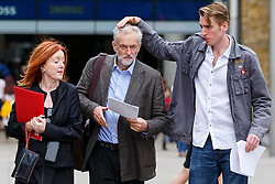 © Licensed to London News Pictures. 18/08/2015. London, UK. Labour Party leader candidate JEREMY CORBYN being prepared with help from his staff before outlining his plans for integrated publicly owned railway network outside King's Cross station in London on Tuesday, August 18, 2015. Photo credit: Tolga Akmen/LNP