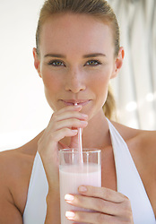 Close up  of a woman drinking a yogurt smoothie with a straw