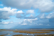 Boats and puffy clouds in blue sky at Cley Next The Sea marshes, Norfolk, UK