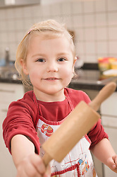 Girl holding rolling pin, smiling, portrait