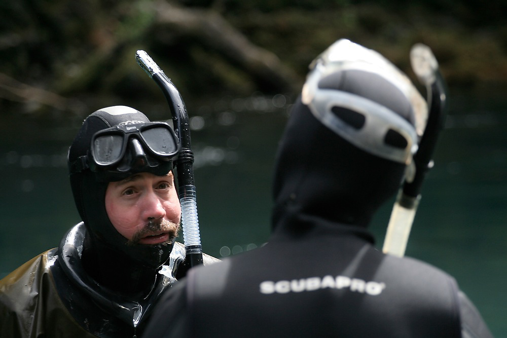 Fish biologist Christian Torgersen talks with James Starr during a snorkel survey of the Elwha River, in Olympic National Park, Washington. The research is a collaborative effort between the National Park Service and other agencies to establish a baseline of fish distribution and habitat structure for the entire river before the removal of the upper and lower dams, scheduled for 2012.
