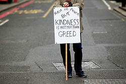 © Licensed to London News Pictures 17/04/2013.A protester holds a sign outside St Paul's Cathedral in central London, where Margaret Thatcher's funeral was being held. .London, UK.Photo credit: Anna Branthwaite/LNP