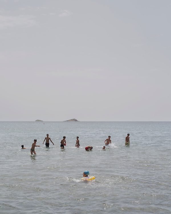 Refugee children swimming in the shallow waters of Gourna Beach. It is the first time they have been back to the sea since they were rescued by the coast guard after crossing from Turkey.