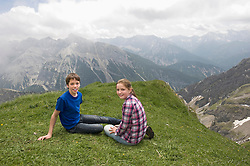 Young girl and boy sitting on grass Alps