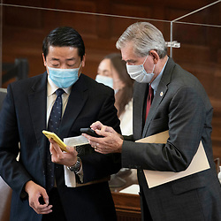 Austin, TX USA March 31, 2021:  State Rep. Gene Wu, D-Houston, and Rep. Ed Thompson, R-Pearland, (r) on the floor of the Texas House of Representatives during routine bill readings at the 87th Texas legislative session. Emergency bills include power company regulation, border security and the coronavirus response.