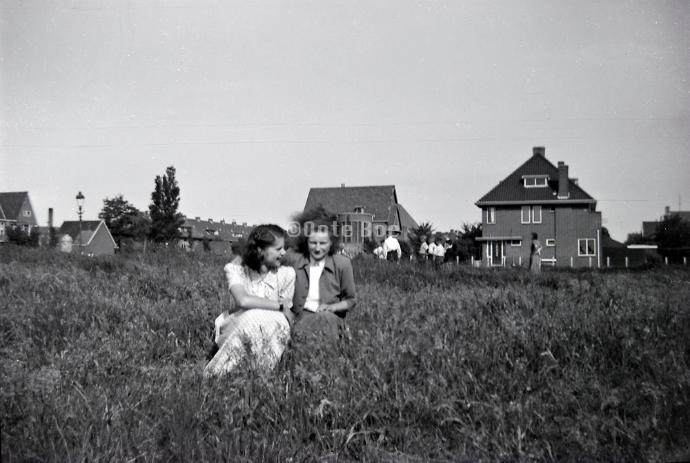 friends sitting in the field at the edge of a new housing development Netherlands 1950s
