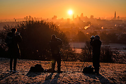 © Licensed to London News Pictures. 29/12/2016. London, UK. Photographers on Parliament Hill on Hampstead Heath London to watch the sunrise over the city of London on another cold winter morning. Most of the UK has woken to freezing temperatures. Photo credit: Ben Cawthra/LNP