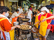 23 SEPTEMBER 2014 - BANGKOK, THAILAND: Women deep fry Chinese meatless snacks on the first day of the Vegetarian Festival near the Chit Sia Ma Chinese shrine in Bangkok. The Vegetarian Festival is celebrated throughout Thailand. It is the Thai version of the The Nine Emperor Gods Festival, a nine-day Taoist celebration beginning on the eve of 9th lunar month of the Chinese calendar. During a period of nine days, those who are participating in the festival dress all in white and abstain from eating meat, poultry, seafood, and dairy products. Vendors and proprietors of restaurants indicate that vegetarian food is for sale by putting a yellow flag out with Thai characters for meatless written on it in red.    PHOTO BY JACK KURTZ