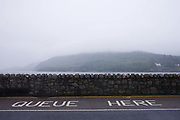 A Queue Here sign on the road at the Corran Ferry crossing  on Inverscaddle Bay, Ardgour, Scotland. On a bleak and grey summer evening, with low clouds descending on surrounding hills and mountains, we see the still waters of this Scottish lake in the background. A stone wall separates the waters from the A861 road that circles this Highland region, from Moidart to nearby Fort William. Here, there is a sea crossing and the 10 minute Corran ferry service runs every 30 minutes from Corran to Ardgour, saving a round-trip of over 30 miles. Motorists are asked to queue (line) up and await the ferry to accept passengers.